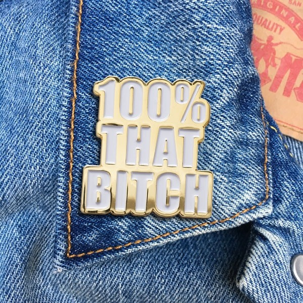 100% That Bitch pinned onto a lapel